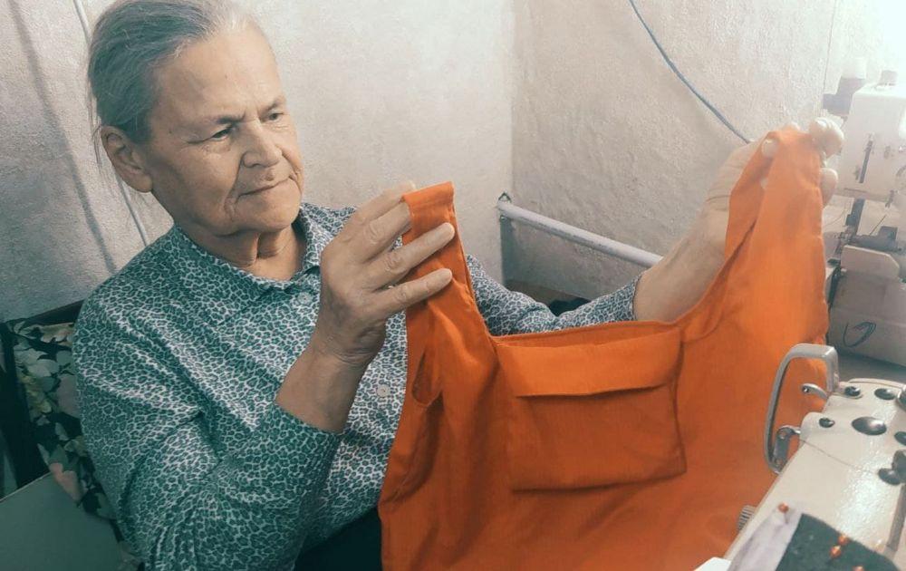 Пожилая женщина шьёт сумку