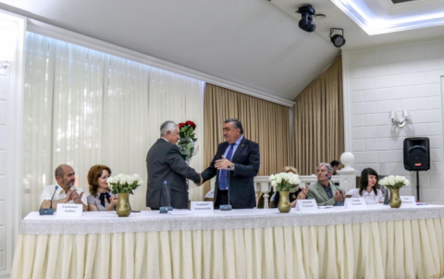 Владимир Семенчишин принимает букет и поздравления от депутата Парламента Владимира Хотиняну.